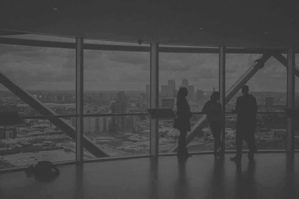 Project Designers Standing Inside Tall Building Looking Out Over The City