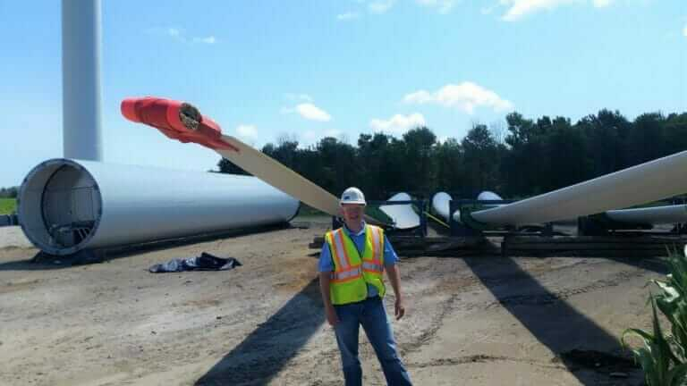 MTC employee in front of wind farm turbine